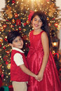 Siblings in red near christmas trees with heart shaped bokeh lights Stock Image