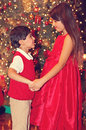 Siblings in red near christmas trees with heart shaped bokeh lights Stock Images