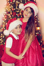 Siblings in red near christmas trees with heart shaped bokeh lights Stock Photos