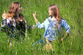 Siblings serious discussion two pretty country teen girls with long brown hair standing in tall grass having a friendly with each Stock Photography