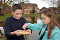 Siblings sharing pastry outside at a little lake a piece of cake Royalty Free Stock Photos