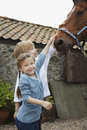Siblings stroking horse outside stable smiling girl and boy Stock Images