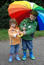 Siblings with umbrella outside a colorful big Royalty Free Stock Photo