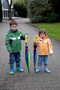 Siblings with umbrella outside a colorful big Royalty Free Stock Photos