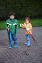 Siblings with umbrella outside a colorful big Royalty Free Stock Image