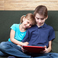 Siblings using a tablet computer children wearing casual clothes playing or watching movie on touch pad at home sitting on green Royalty Free Stock Image