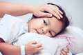 Sick asian child girl is lying in bed and mother touch forehead