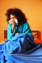 Sick in bed woman sitting under a blue blanket her blowing her nose a paper tissue Royalty Free Stock Photos