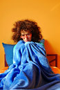 Sick in bed woman sitting under a blue blanket her feeling cold and Stock Image
