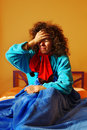 Sick in bed woman sitting under a blue blanket her holding her forehead pain Royalty Free Stock Photos