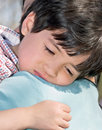 Sick boy four year old is and resting quietly on his mothers shoulder outdoors natural light Royalty Free Stock Photo