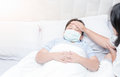 Sick boy with hygienic mask laying on bed Royalty Free Stock Photo