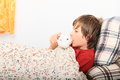Sick boy kid lying in a bed on pillows under blanket with flowers and drinking cup of tea Stock Images