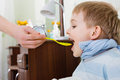 Sick boy taking medicine from spoon at home Royalty Free Stock Photography