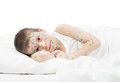 Sick boy in white bed lying Royalty Free Stock Photos