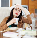 Sick brunnette girl with drugs at table in living room Stock Photos