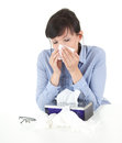 Sick businesswoman with flu blowing nose in tissue Stock Photos