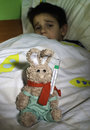 Sick child in bed with teddy bear measuring the temperature a thermometer Royalty Free Stock Images