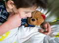 Sick child in bed with teddy bear measuring the temperature a thermometer Royalty Free Stock Image