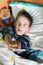 Sick child in bed with teddy bear measuring the temperature a thermometer Stock Photos