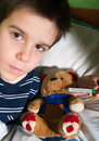 Sick child in bed with teddy bear measuring the temperature a thermometer Royalty Free Stock Photography