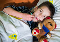 Sick child in bed with teddy bear measuring the temperature a thermometer Stock Photography
