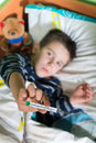 Sick child in bed with teddy bear measuring the temperature a thermometer Stock Photo