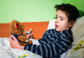 Sick child in bed with teddy bear measuring the temperature a thermometer Stock Images