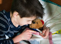 Sick child in bed with teddy bear measuring the temperature a thermometer Royalty Free Stock Photos