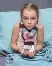 Sick child with pills in hand hands sitting a bed Royalty Free Stock Images