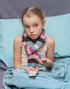 Sick child with pills in hand hands sitting a bed Stock Image