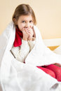 Sick girl wrapped in blanket coughing in bed portrait of Royalty Free Stock Photography