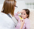 Sick kid with high fever laying in bed and doctor taking temperature Royalty Free Stock Photo