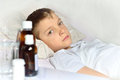 Sick little boy in the bed and medicine on table Royalty Free Stock Photography