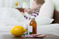 Sick little boy lying in bed pills and lemon on foreground Royalty Free Stock Photo
