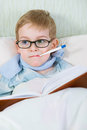 Sick little boy lying in bed with thermometer and reading book Royalty Free Stock Image