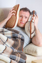 Sick man holding head on pillows concept of headache overworked pain Royalty Free Stock Image