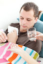 Sick man taking medicine on the sofa Royalty Free Stock Photos