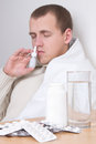 Sick man using nasal spray in living room young Stock Photo