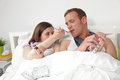Sick married couple in bed suffering from seasonal flu and colds with scarves around their necks and the wife feeding her husband Royalty Free Stock Photo