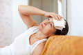 Sick mature woman having headache holding towel on her head Royalty Free Stock Photos