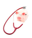 Sick piggy bank with stethoscope over white background Royalty Free Stock Photos