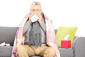 Sick senior man sitting on a sofa and blowing his nose covered with blanket isolated white background Royalty Free Stock Photo