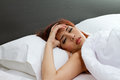 Sick woman on bed portrait of showing symptom of cold flu insomnia stress headache hangover or dizziness Royalty Free Stock Photos