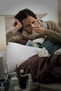 Sick woman with flu sneezing in bed blowing her nose Stock Photo
