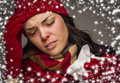 Sick woman with tissue and snow effect surrounding mixed race wearing winter hat gloves a her Royalty Free Stock Images