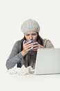 Sick woman in winter attire with laptop and tea close up tired gray working her while drinking a cup of hot isolated on white Royalty Free Stock Photography