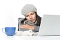 Sick woman in winter attire with laptop and tea close up tired gray working her while having cup of hot on desk isolated on white Royalty Free Stock Images