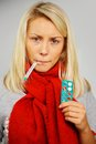 Sick young blond woman with thermometer pills and Royalty Free Stock Photography