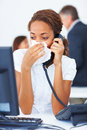 Sick young business woman blowing her nose Stock Image